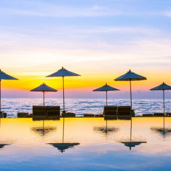 umbrella-and-chair-around-swimming-pool-in-resort--X4LVCBU