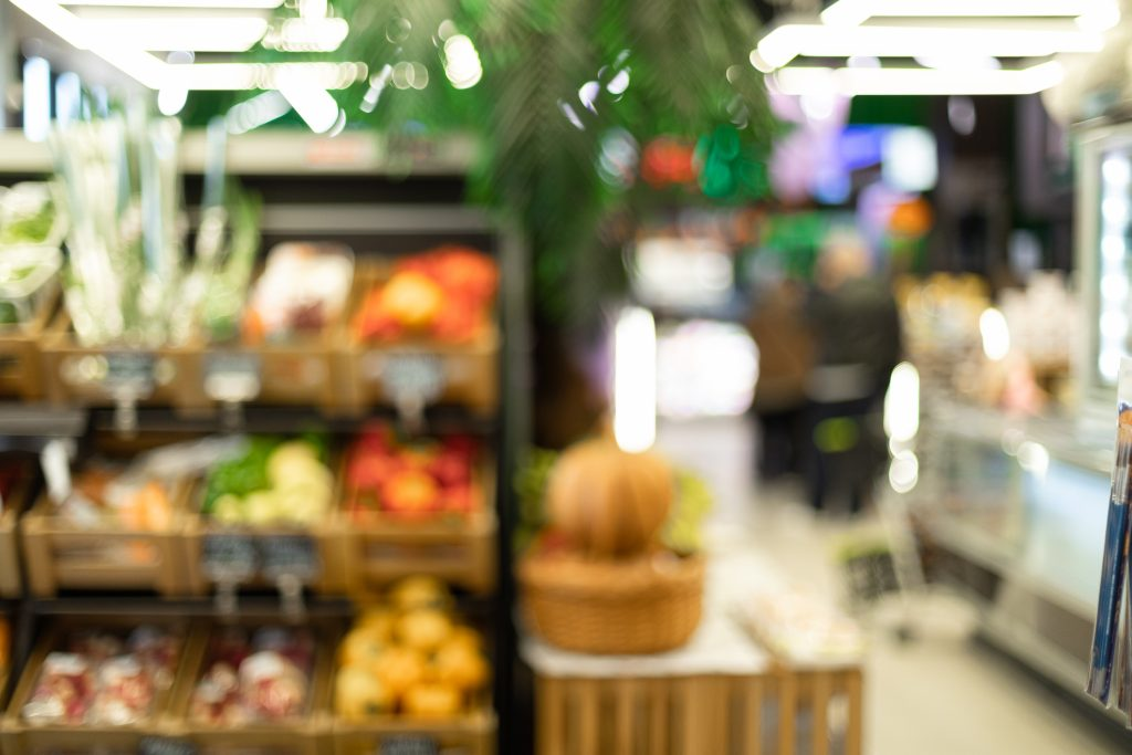 Blurred Supermarket Aisle Background Of Vegetables Department In Grocery Store