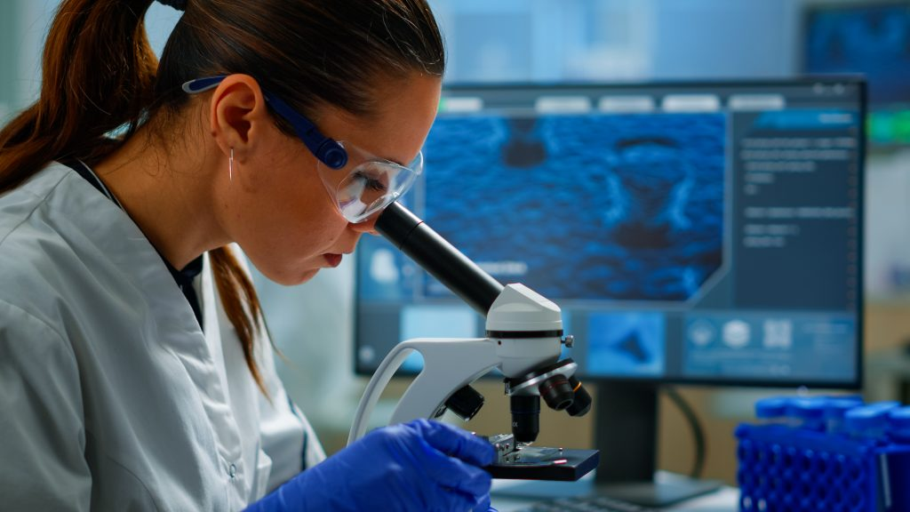 Portrait of scientist looking under microscope in medical lab