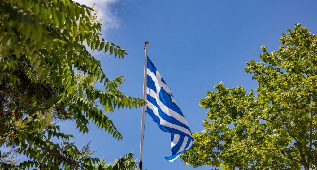 greek-flag-waving-against-blue-sky-background-7ZVUWAS