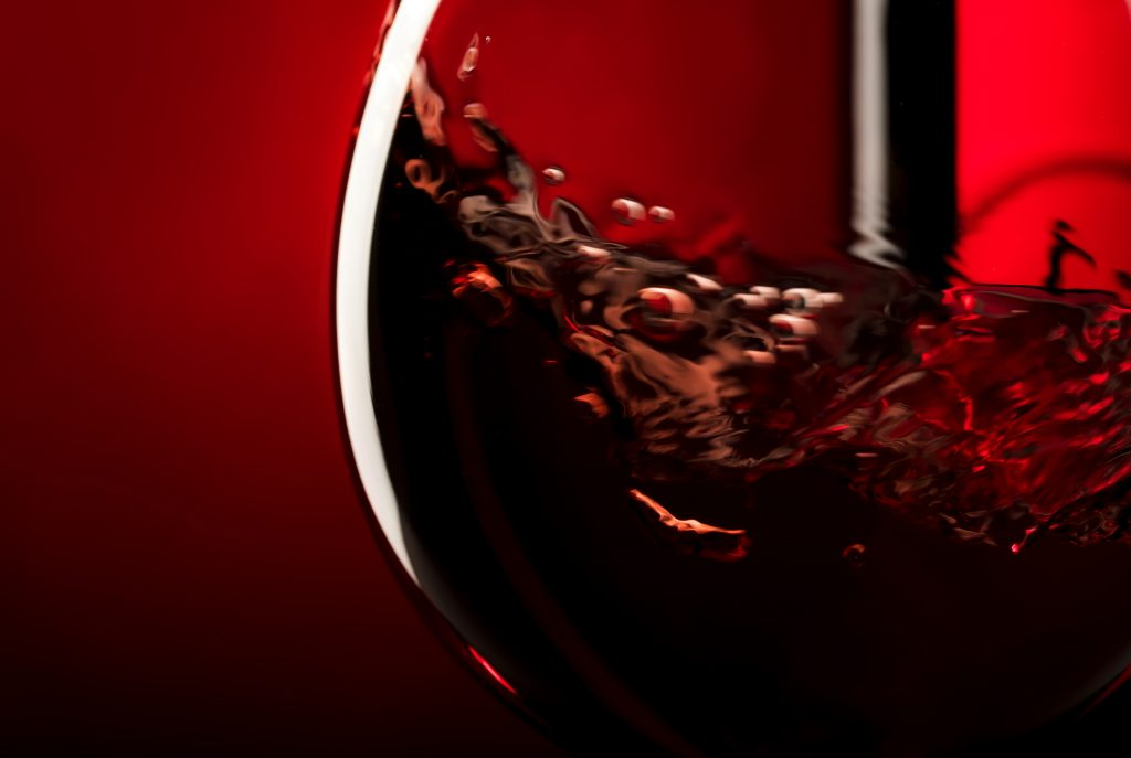 Red wine on red black background, abstract splashing. Macro shot
