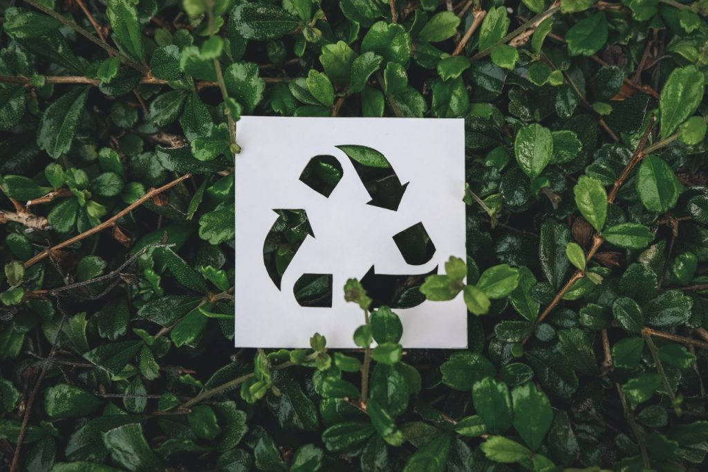 recycle-symbol-created-with-paper-cut-on-green-lea-MAKDWWB