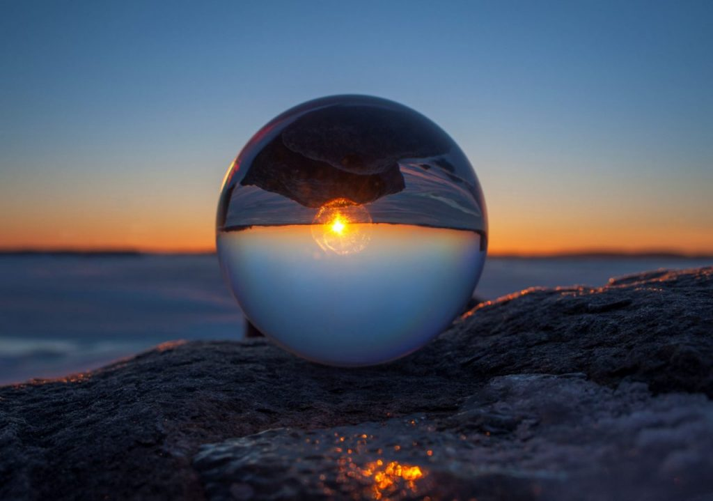 close-up-of-sunset-horizon-inverted-in-glass-spher-34NNDVH