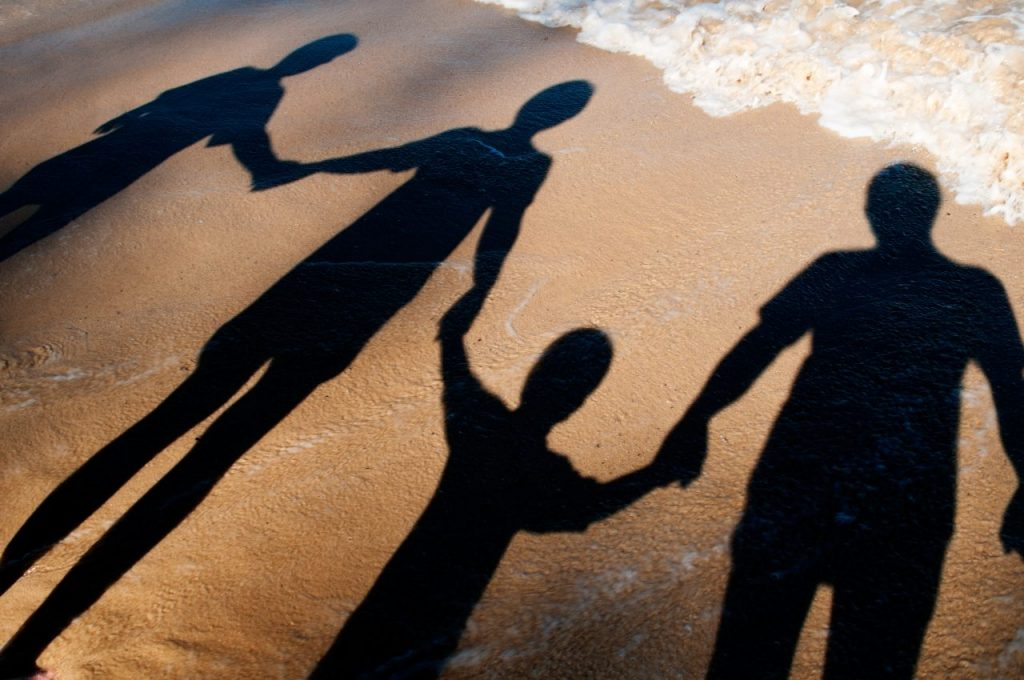 shadow-of-adults-and-children-holding-hands-on-the-DNSJC4B