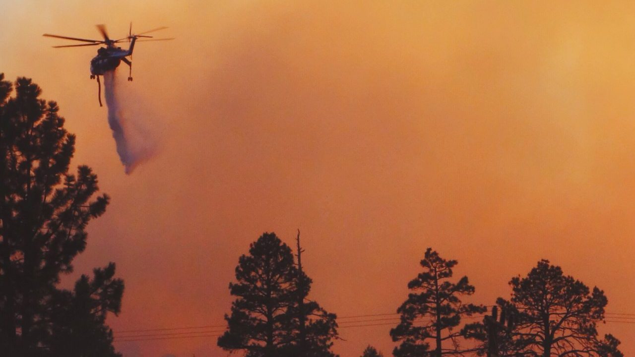 a-helicopter-dumps-water-on-a-forest-fire-JCHSS3E