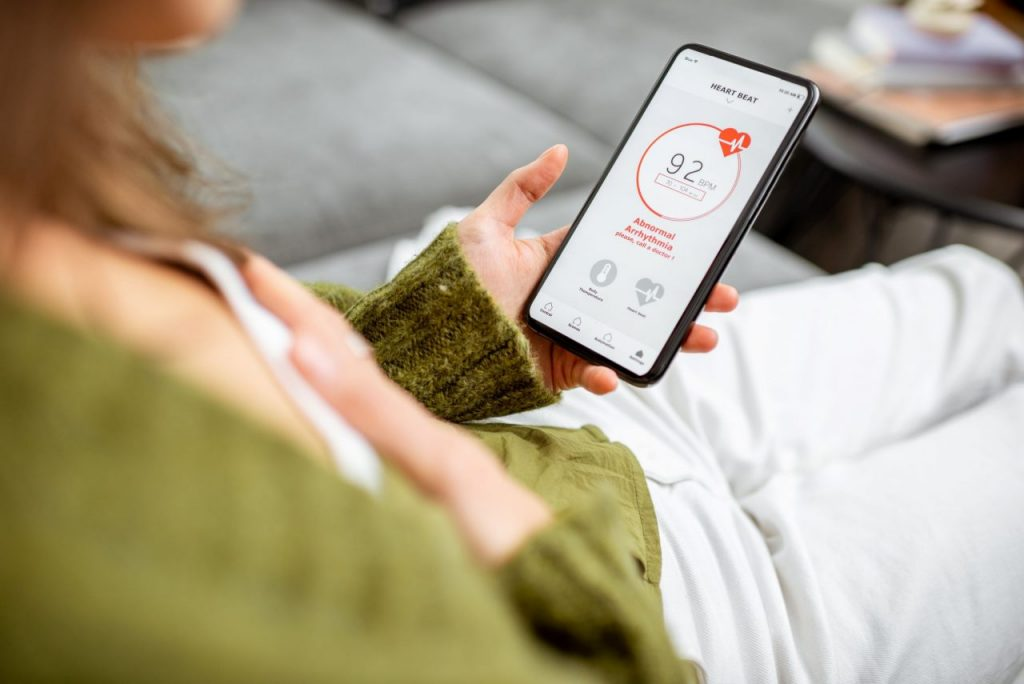 woman-measuring-heart-beat-with-a-smart-phone-LYF3AGB